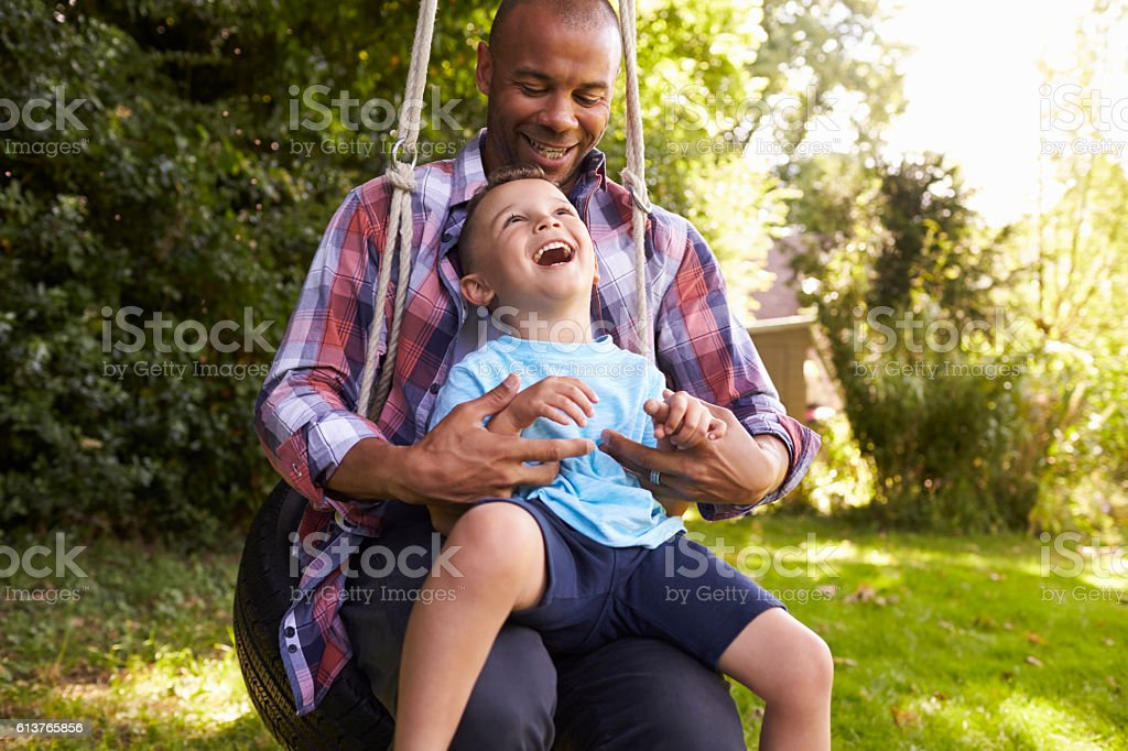 Father And Son Having Fun On Tire Swing In Garden stock photo
