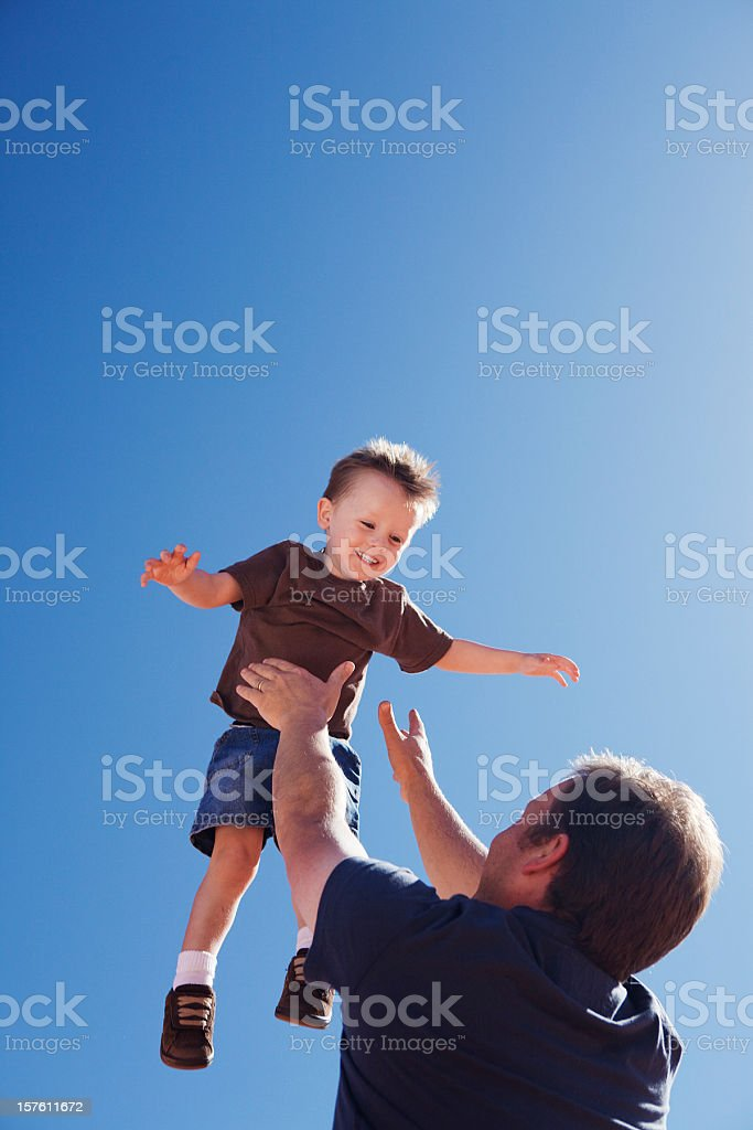 Father and son having fun outdoors under blue sky, copyspace stock photo