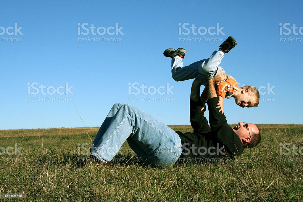 Father and Son Having Fun Playing outside in Open Field royalty-free stock photo