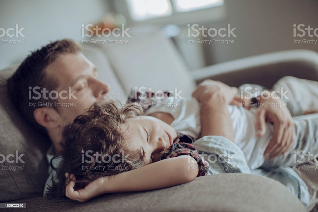 Father and son having nap stock photo