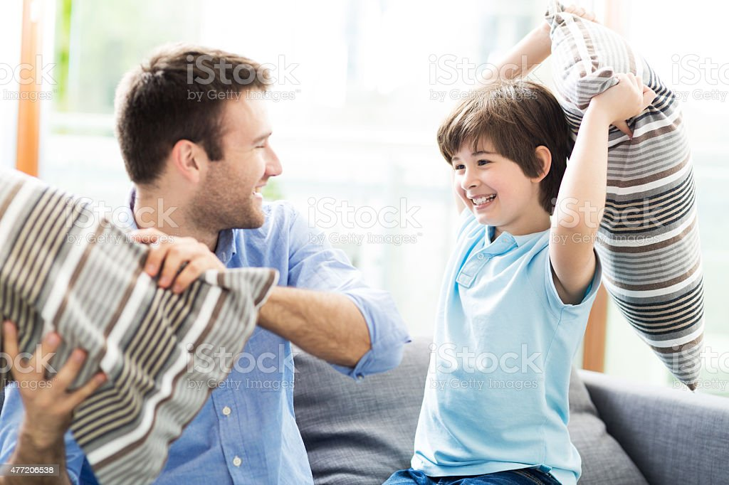 Father and son having pillow fight stock photo