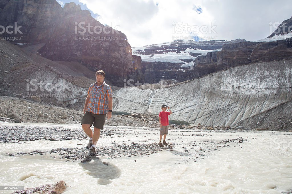 Father and son hike below glaciated mountains, river stock photo