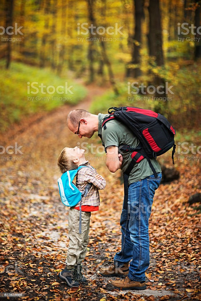 Father and son hiking in autumn beech forest stock photo
