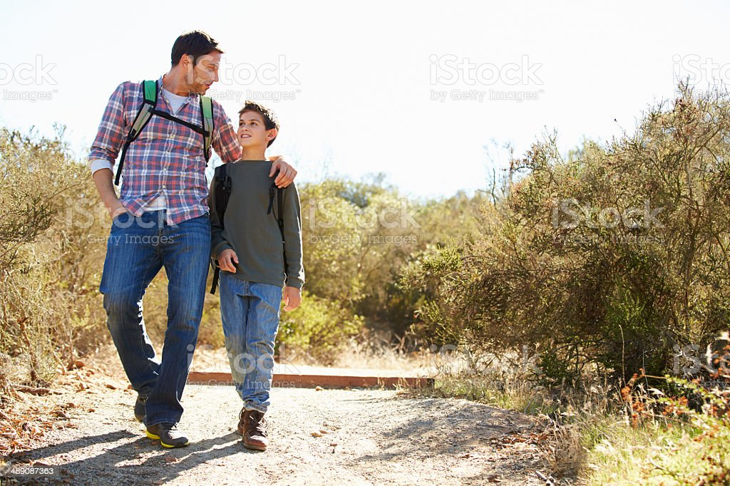 Father and son hiking in the countryside stock photo
