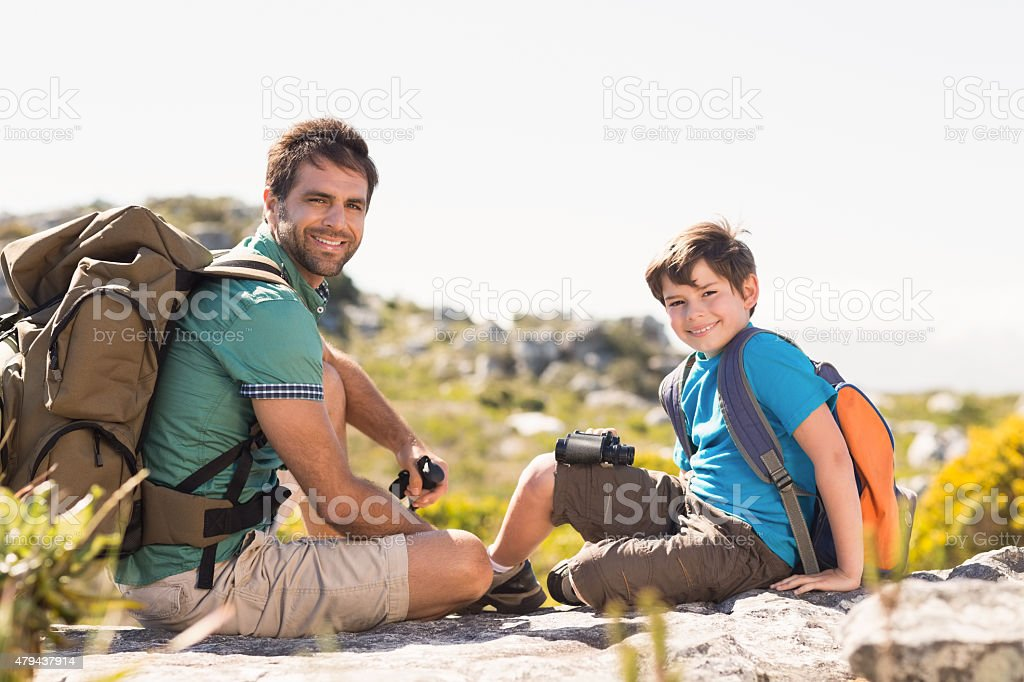 Father and son hiking through mountains stock photo