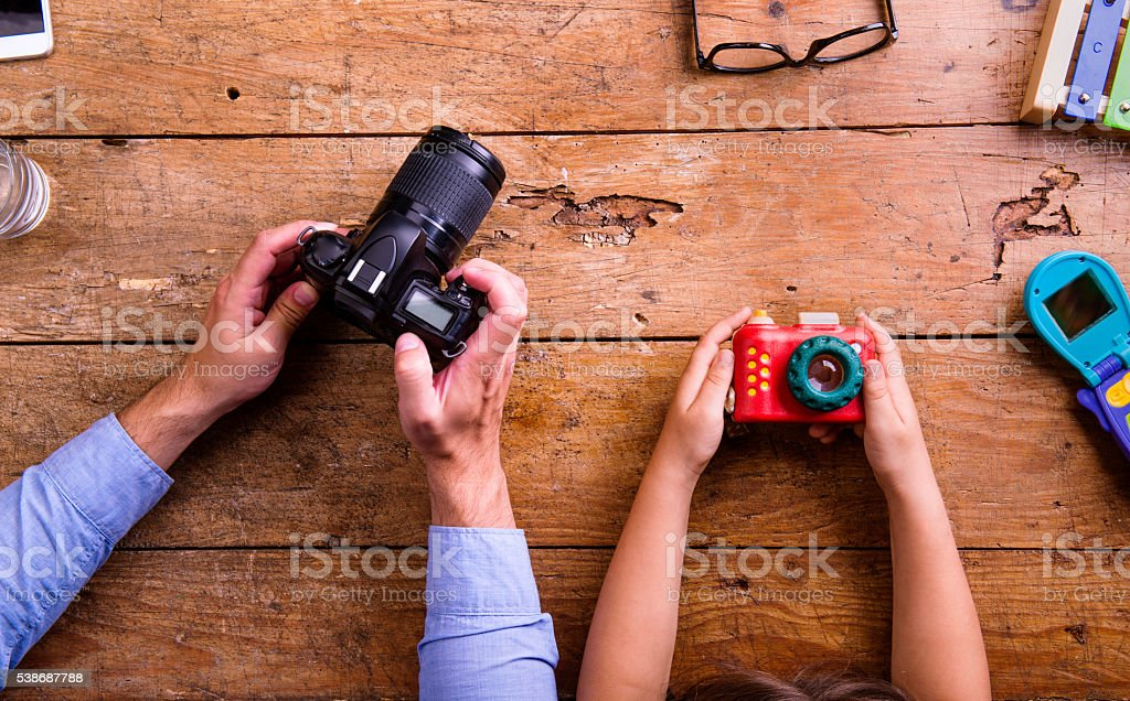Father and son holding cameras, old wooden office desk stock photo