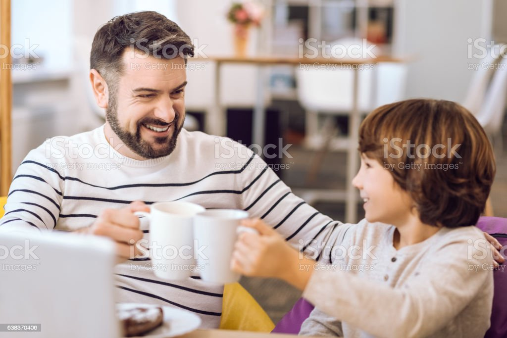 Father and son holding cups with tea stock photo