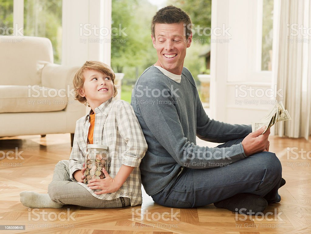 Father and son holding money sitting back to back stock photo