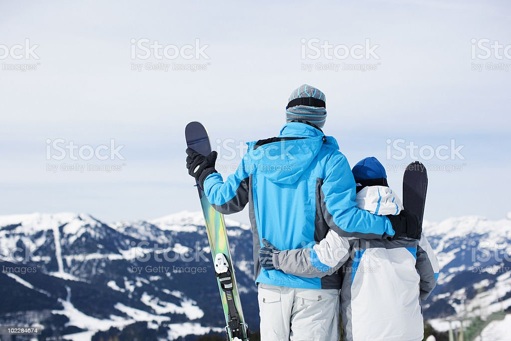 Father and son holding skis on mountain top royalty-free stock photo