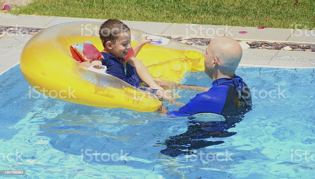 Father and son in a swimming pool royalty-free stock photo