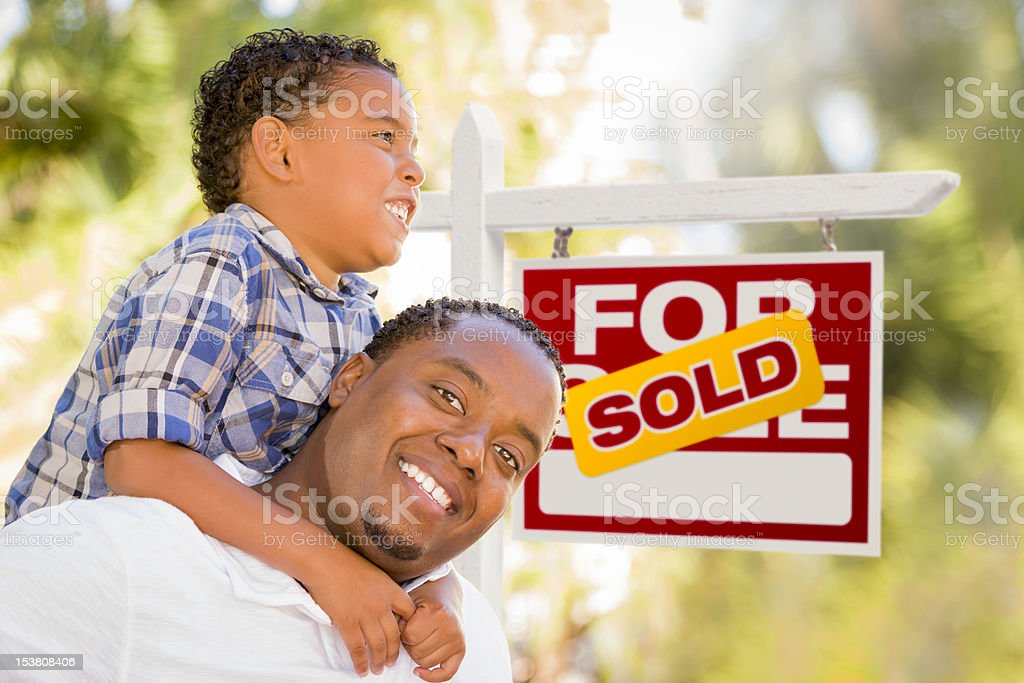 Father and Son In Front of Sold Real Estate Sign royalty-free stock photo