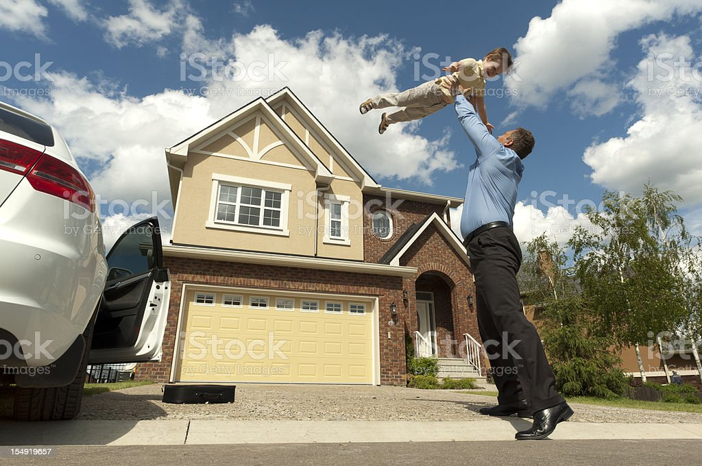 Father and son in front of their new suburban house stock photo