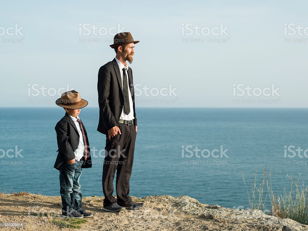 Father and son in similar clothes stock photo