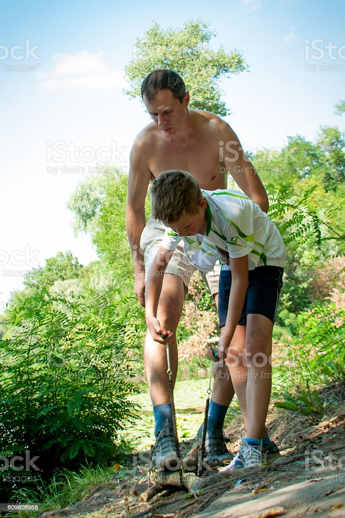 father and son is sawing wood stock photo