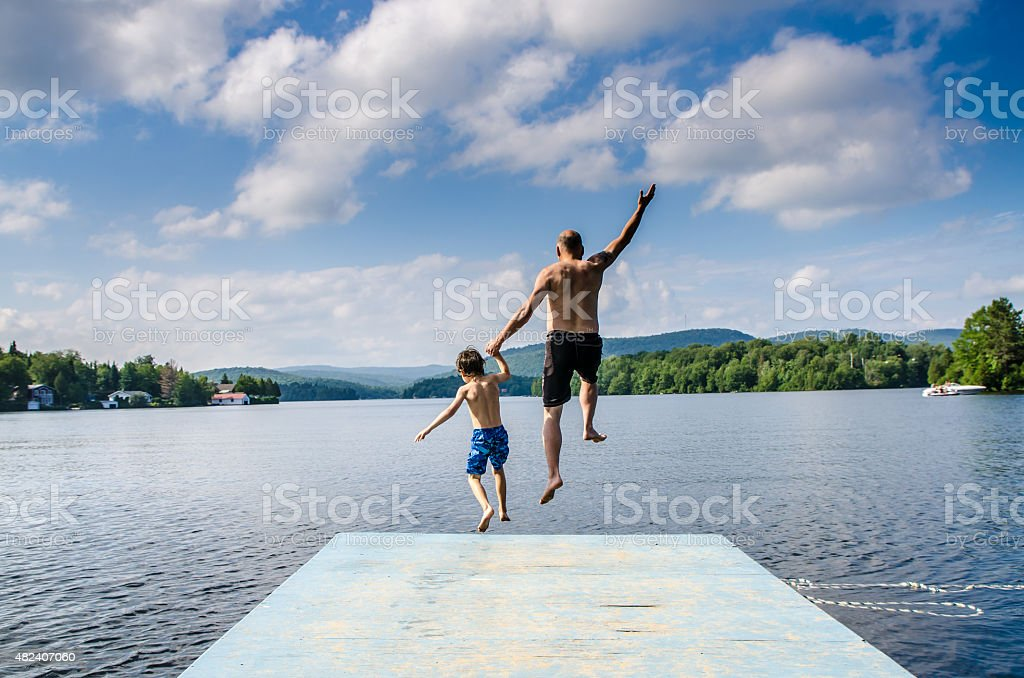 Father and son jumping in lake stock photo