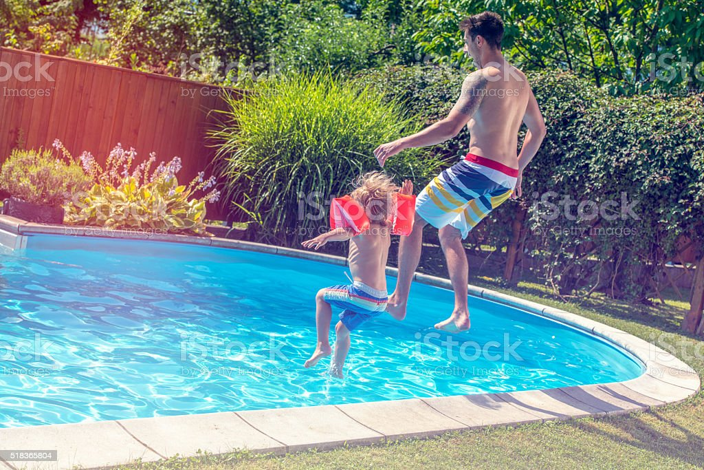 Father and son jumping into a pool stock photo