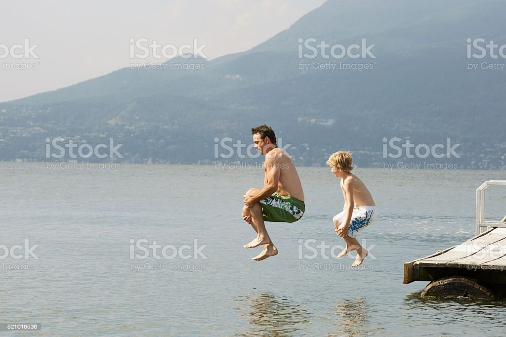 Father and son jumping off a dock stock photo