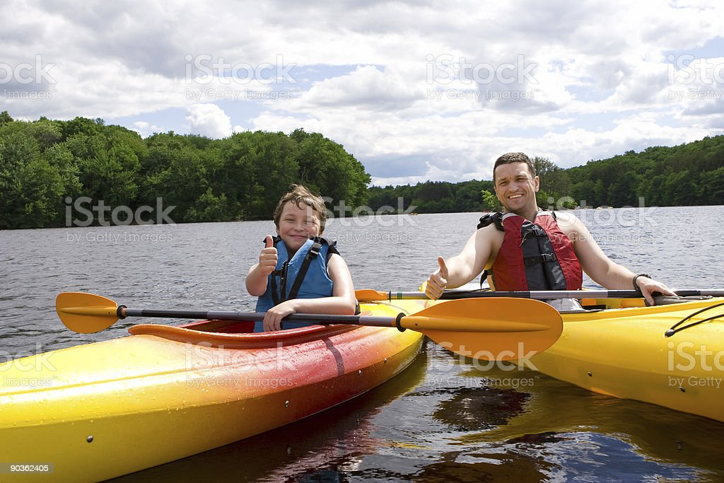 Father and son kayaking and giving a thumbs up sign royalty-free stock photo