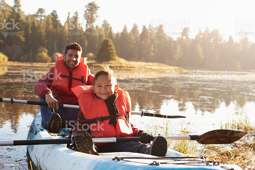 Father and son kayaking on rural lake, close up stock photo