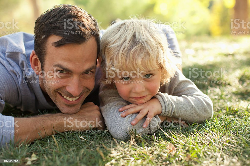Father and son laying in grass together royalty-free stock photo
