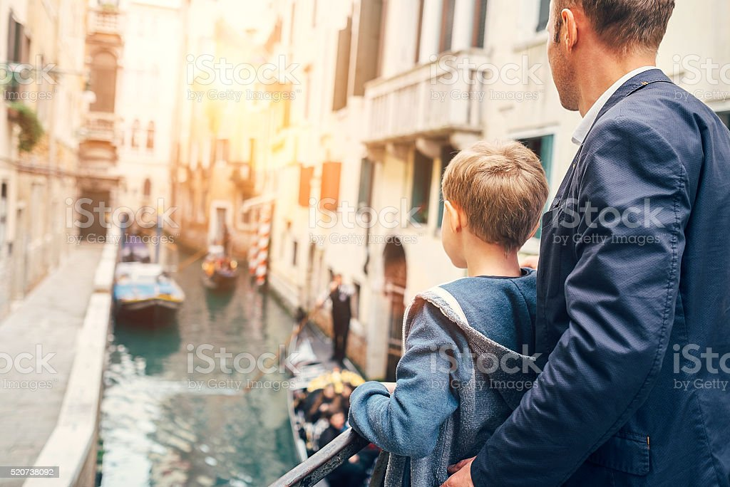 Father and son look together on venecian gondolas stock photo