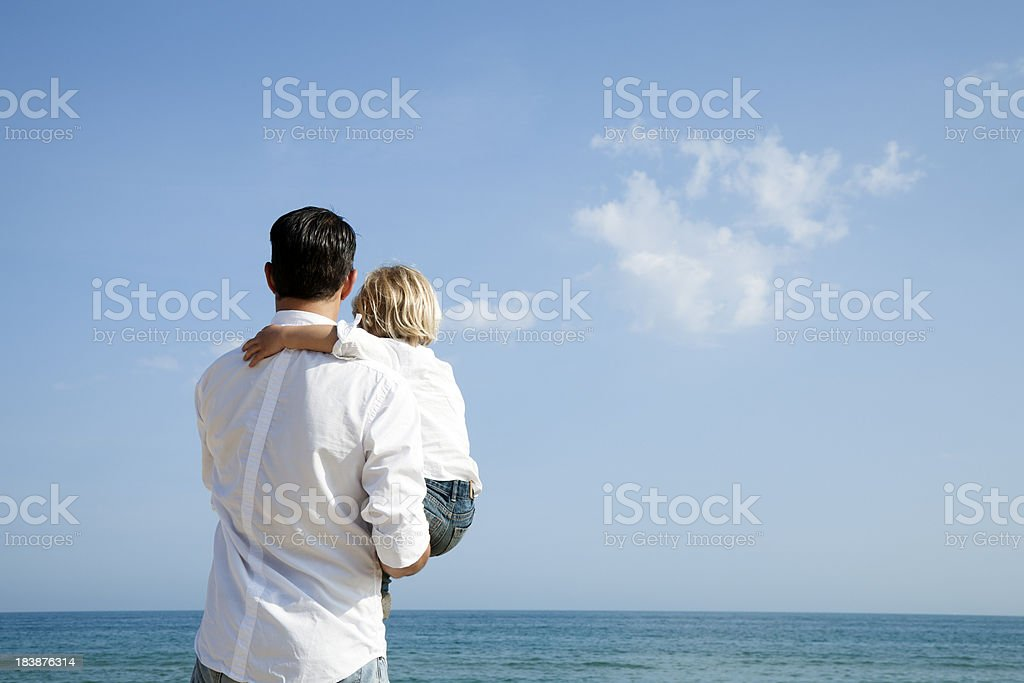 Father and son lookin g to the horizon stock photo