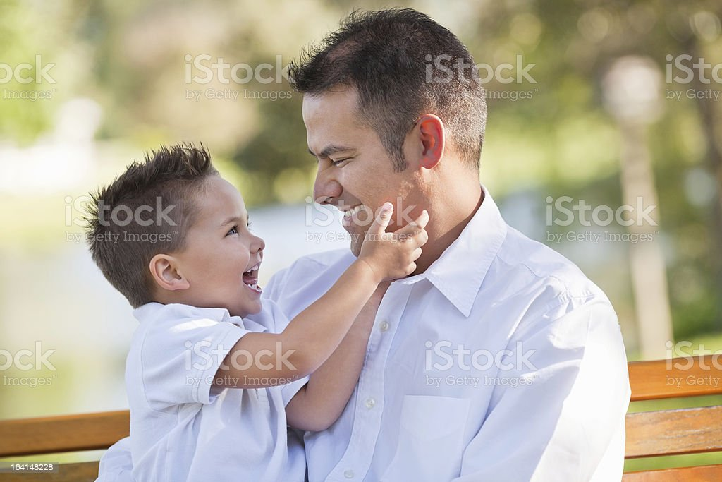 Father And Son Looking At Each Other In Park stock photo
