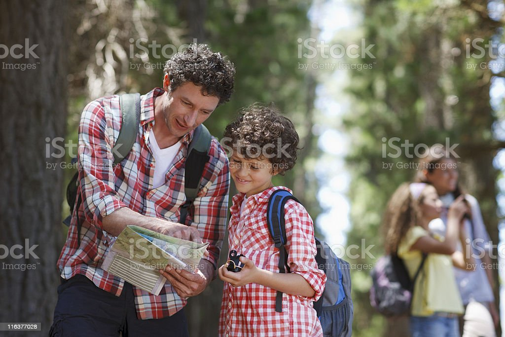 Father and son looking at map in woods royalty-free stock photo
