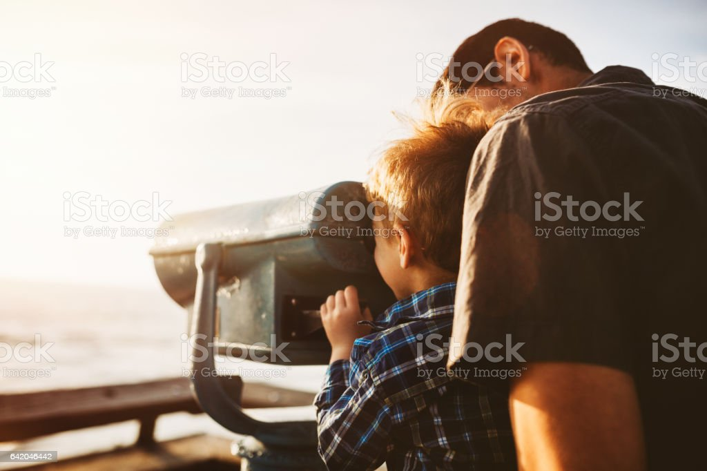 Father and Son Looking At Ocean View stock photo