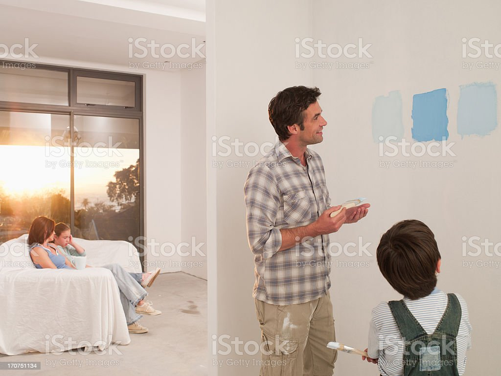 Father and son looking at paint samples on wall royalty-free stock photo