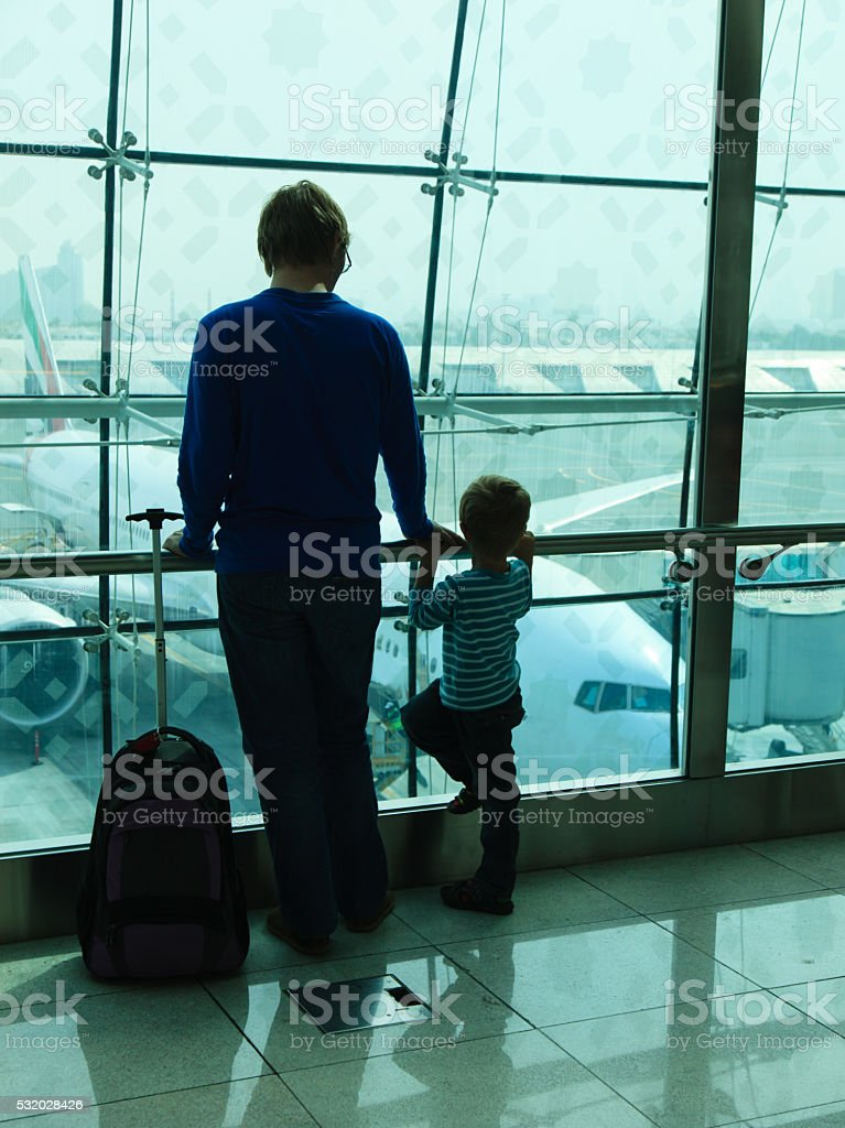 father and son looking at planes in the airport stock photo