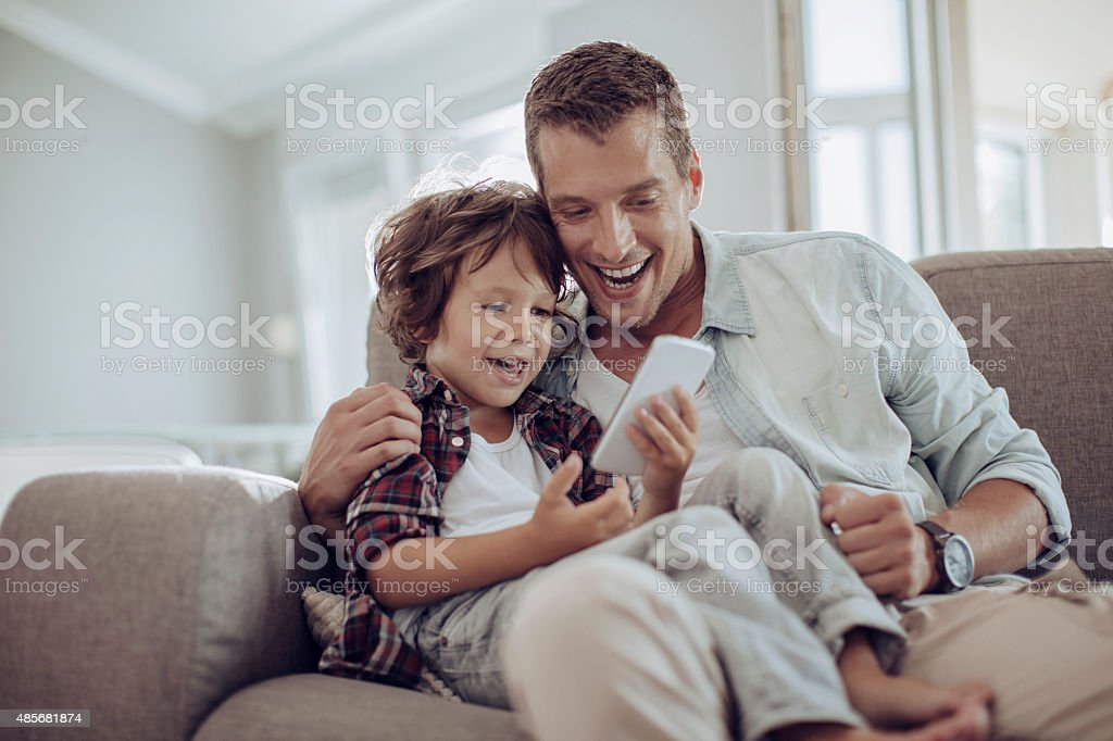 Father and son looking at smart phone stock photo