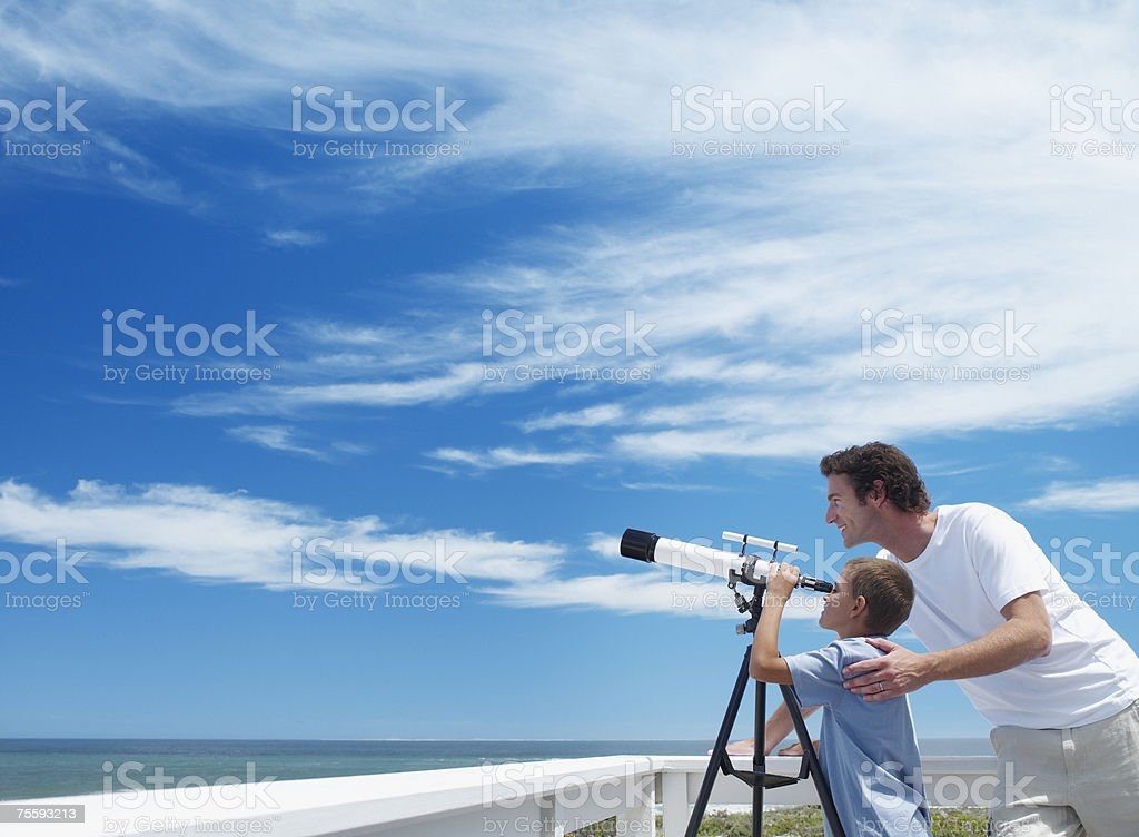 Father and son looking through a telescope stock photo