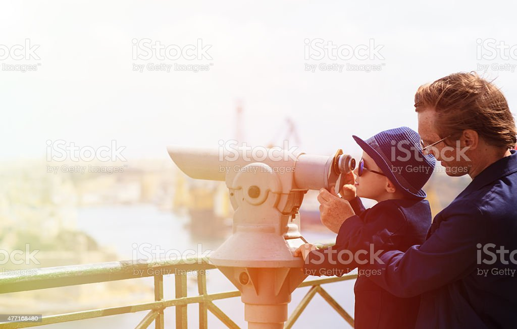 father and son looking through binoculars at the city stock photo