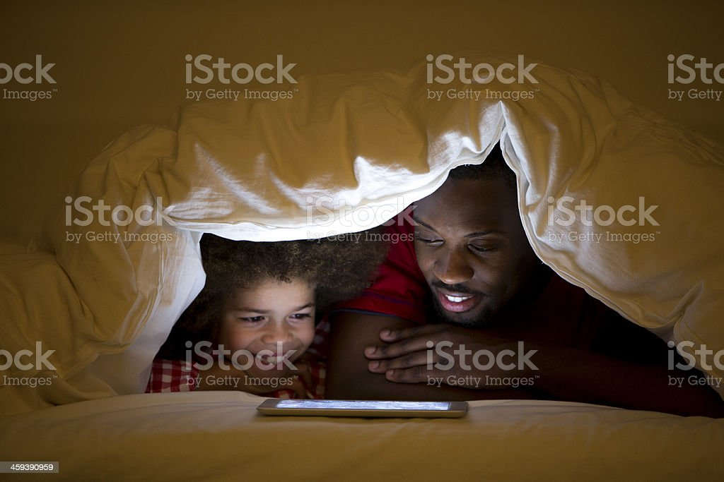 Father and Son lying in bed stock photo