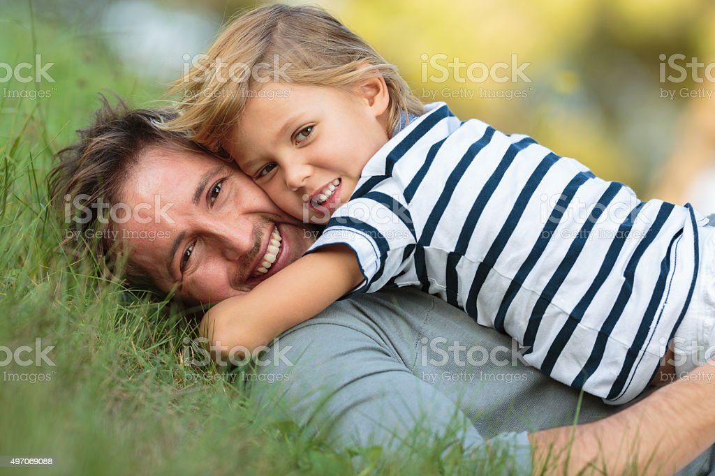 father and son lying in the gras stock photo