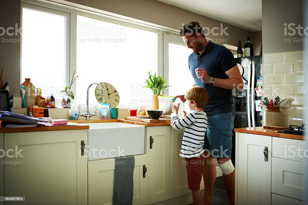 Father and son making breakfast stock photo