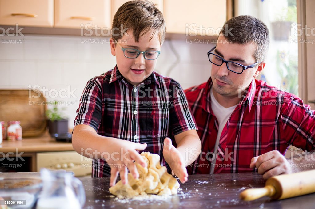 Father and son making cookies stock photo