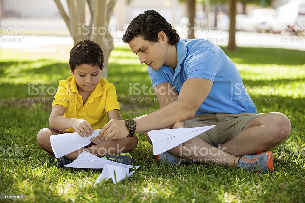 Father and son making paper planes stock photo