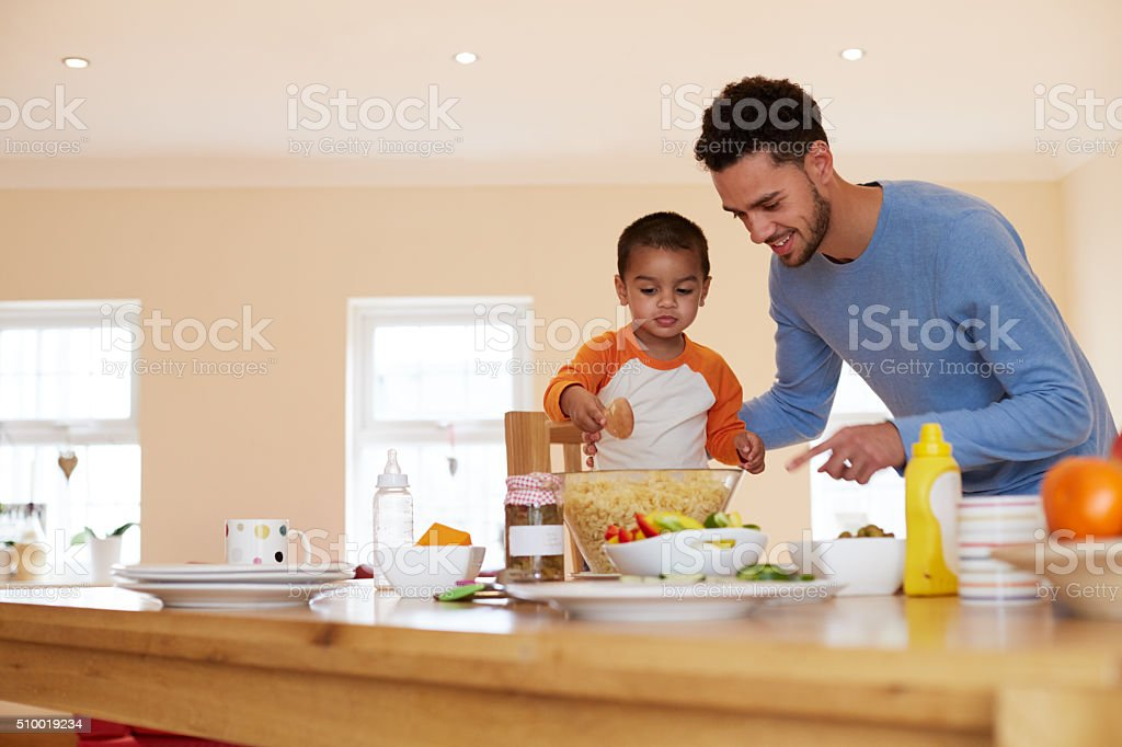 Father And Son Making Pasta Salad In Kitchen stock photo