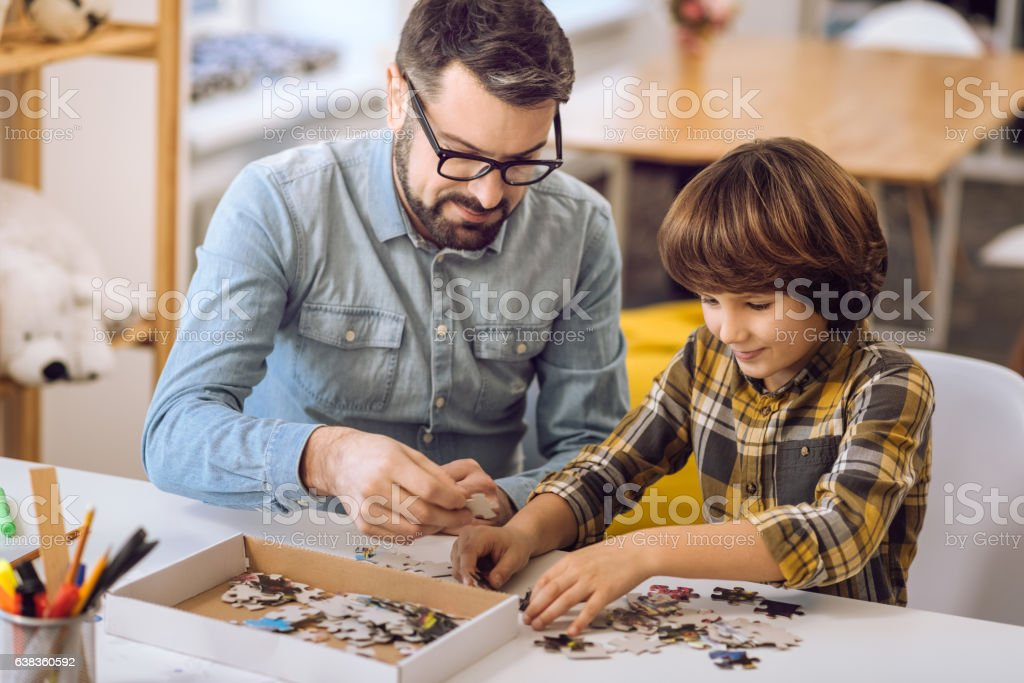Father and son making picture of puzzles stock photo