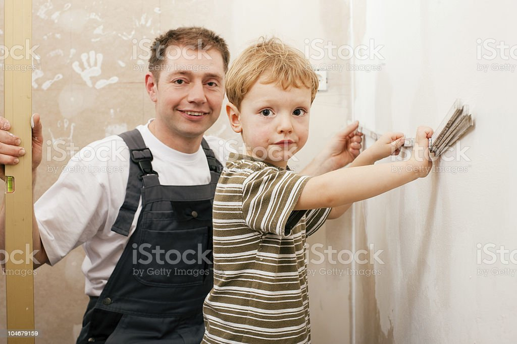 Father and son measuring dry wall royalty-free stock photo