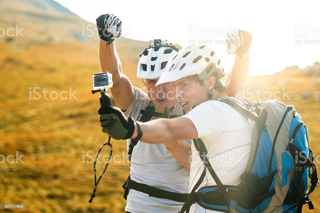 Father and son mountain bikers taking a selfie stock photo