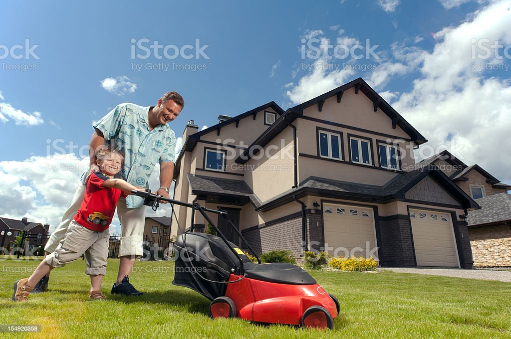 Father and son mowing in front of their suburban house. stock photo