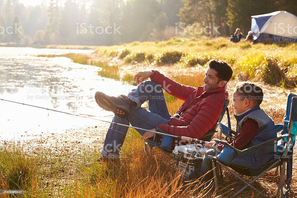 Father and son on a camping trip fishing by a lake stock photo