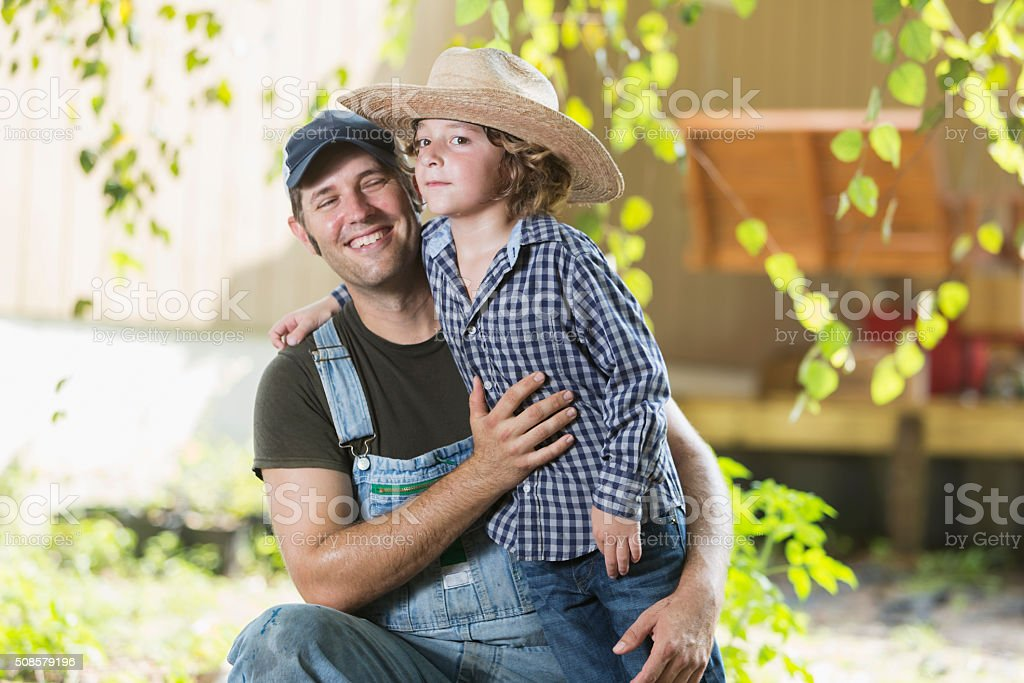 Father and son on family farm smiling stock photo