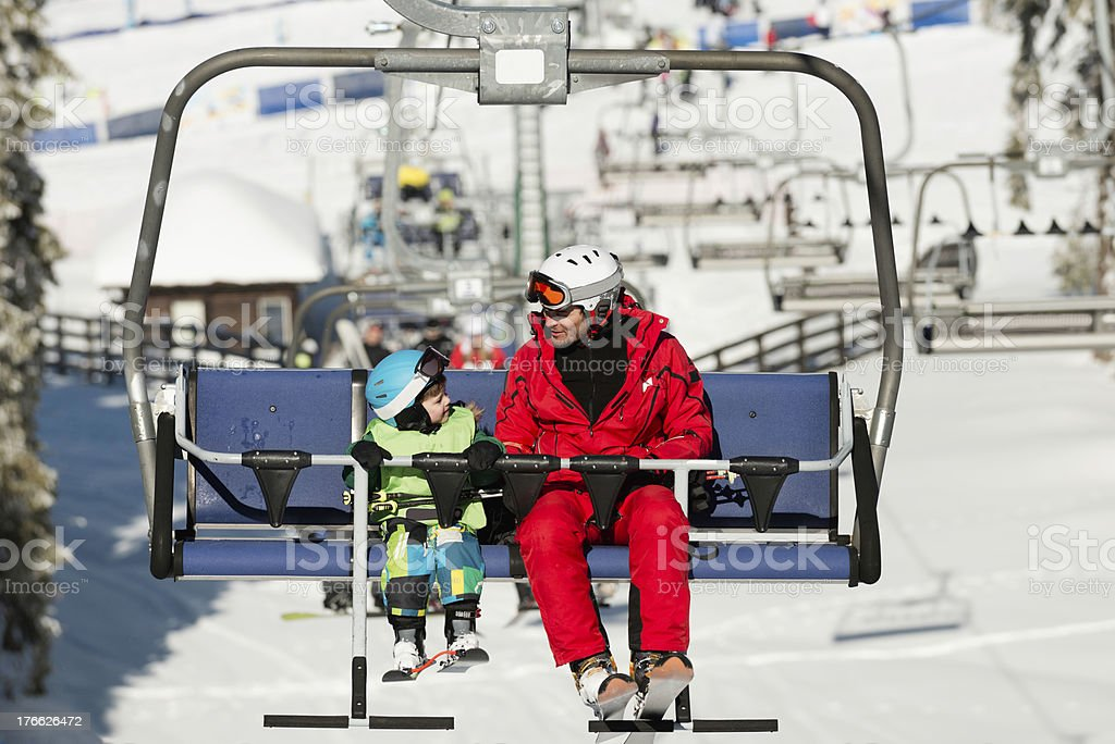 Father and son on ski lift royalty-free stock photo