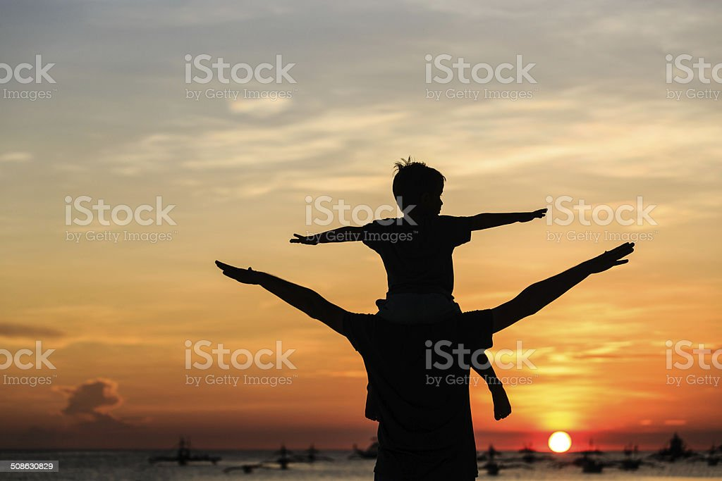 father and son on sunset beach stock photo