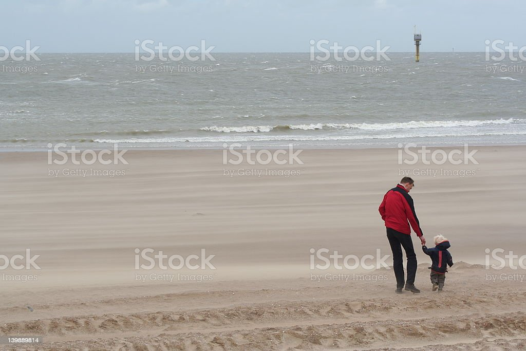 father and son on the beach stock photo