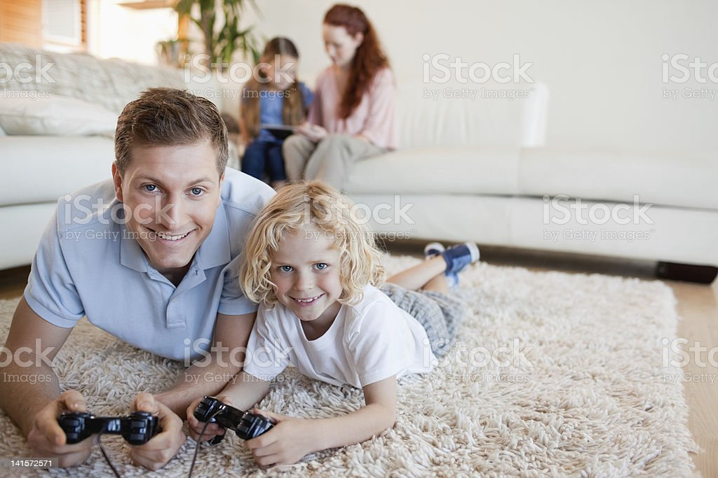 Father and son on the floor playing video games royalty-free stock photo